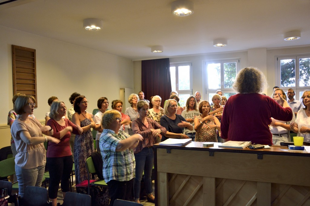 Vor der Probe müssen die Gospelsängerinnen und -sänger sich aufwärmen. Foto: BSM