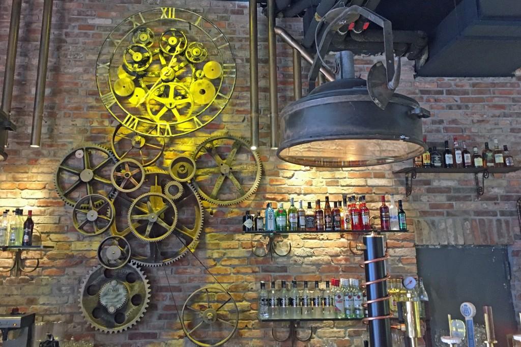 Eine Uhr aus offenen Zahnrädern über der Bar in der Liebeskuh. Foto: BSM