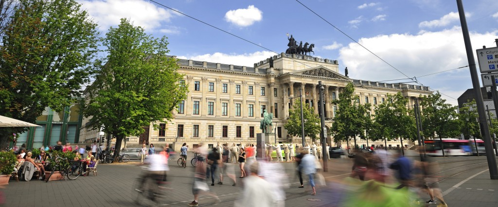 Das Braunschweiger Residenzschloss mit Quadriga, Passanten und Reiterstandbild.