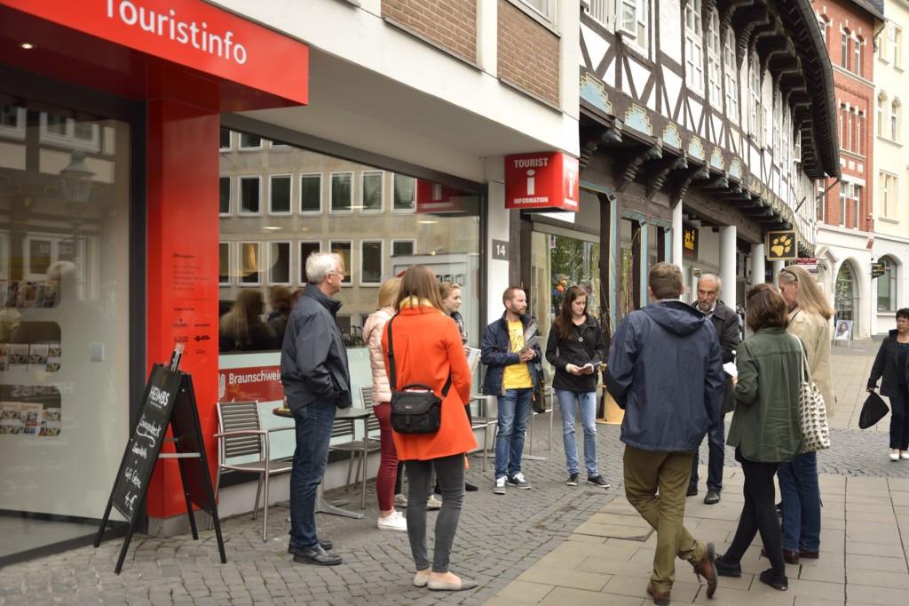 Eine Gruppe Menschen steht vor der Touristinformation Braunschweig.