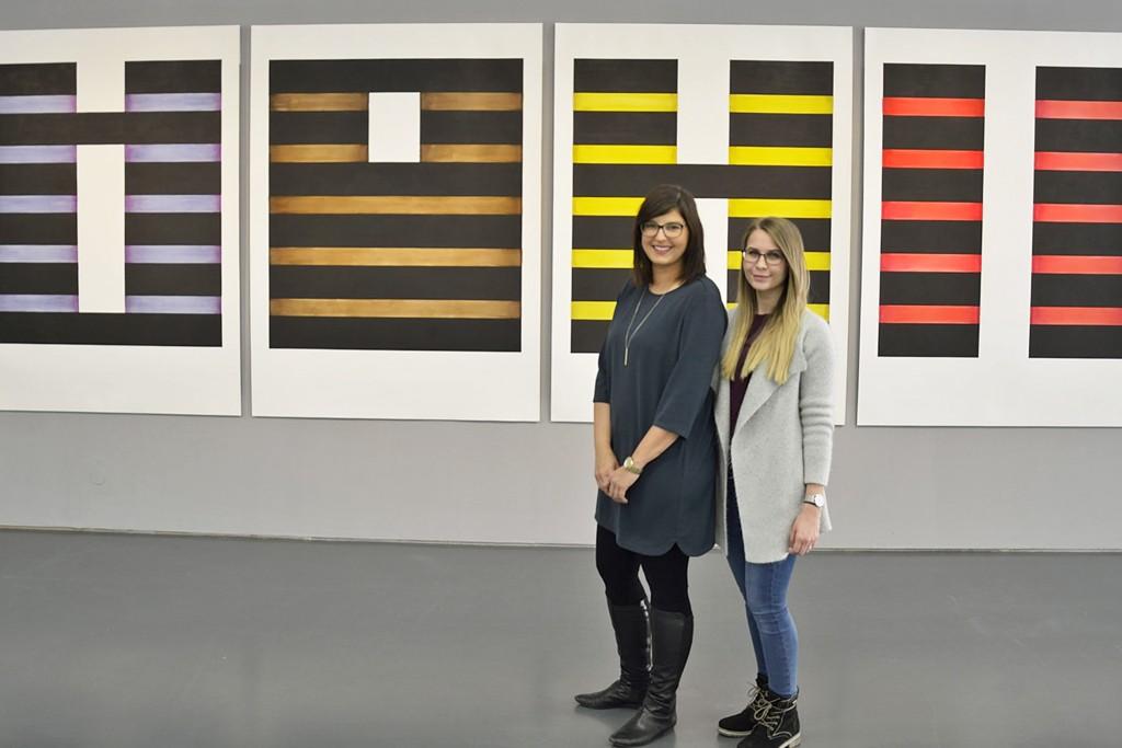 """Sara Kleinwecher und Lisanne Rinke vor den Tuschezeichnungen """"Nullserie I-VI"""", in denen sich Hanna Nitsch mit Farben, Formen und einem Kodierungssystem auseinandersetzt."""