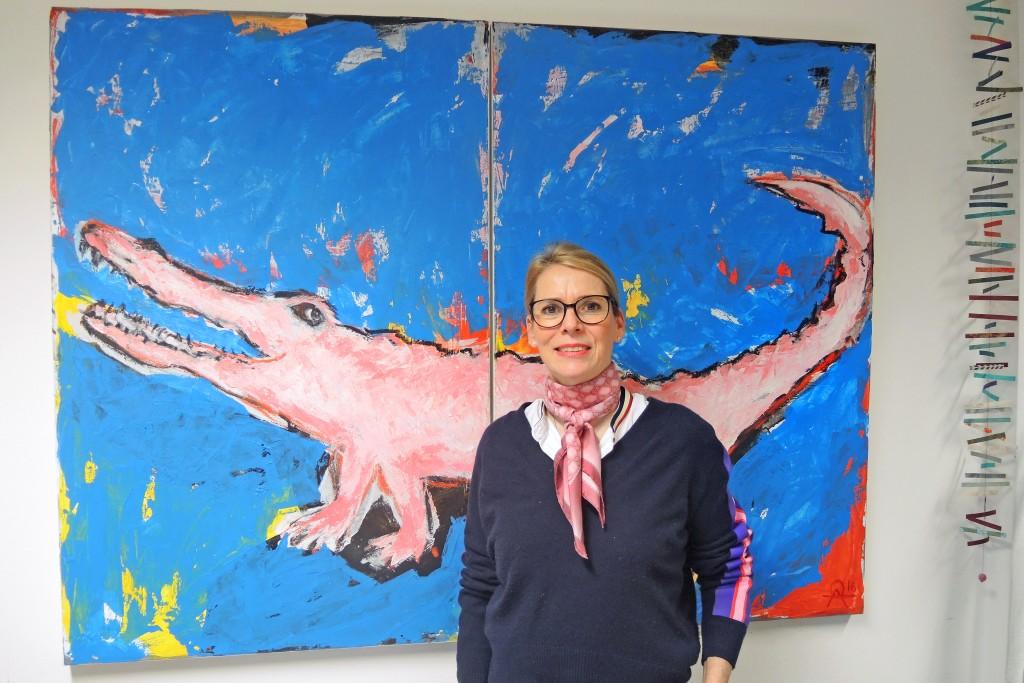Delia Rauls vor einem Bild von einem rosa Krokodil.