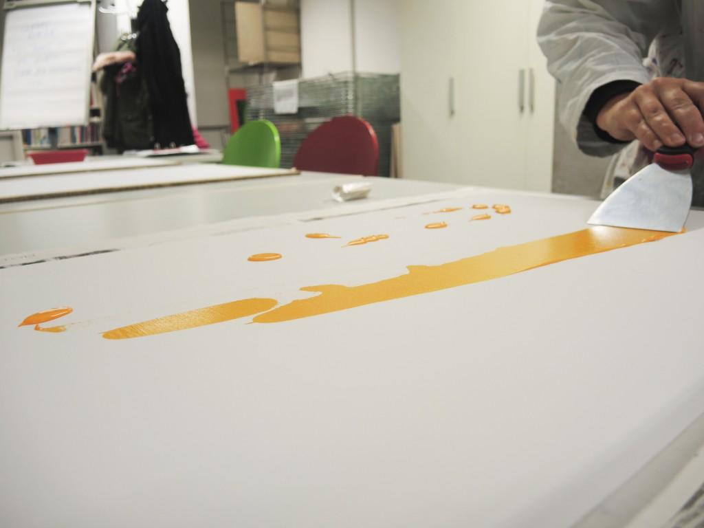 Orangene Farbe wird auf weißer Leinwand gespachtelt