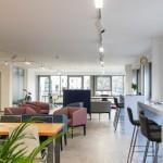 Mit bequemen Sessel, hohen Tischen und etwas grün ist der lichtdurchflutete Raum im BlueWorking stilsicher eingerichtet. Foto: Stephen Dietl
