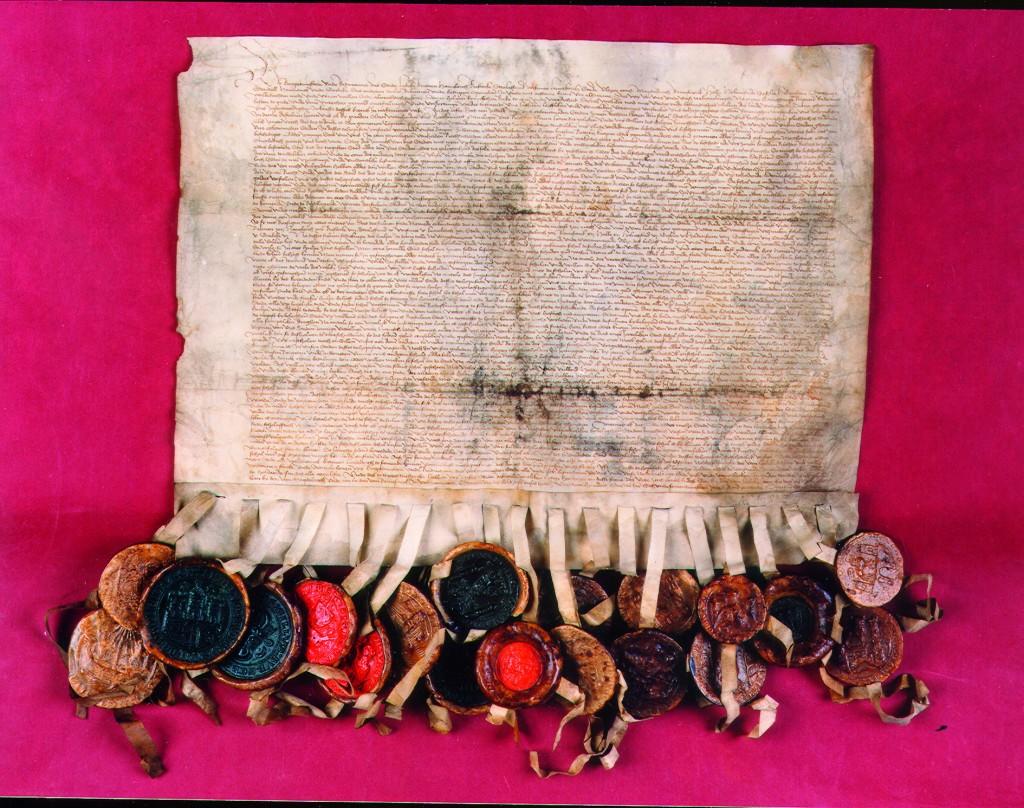 Historische Urkunde mit vielen bunten Siegeln.