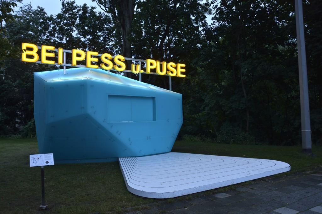Blauer Pavillon mit neongelber Schrift: Bei Pess u. Puse