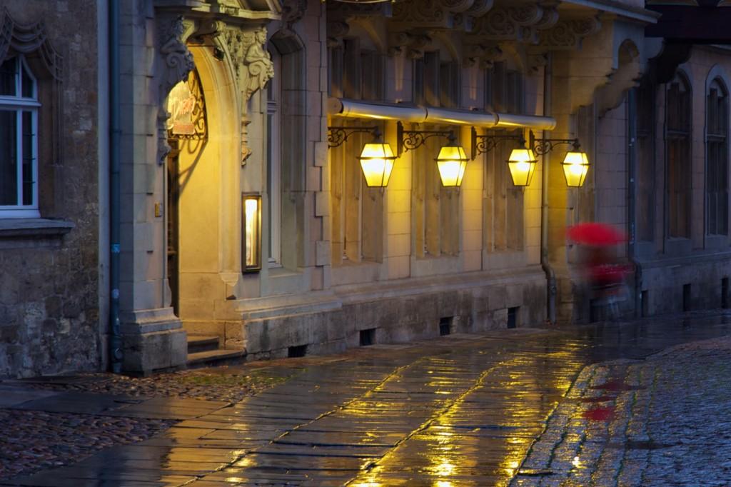 Vier Laternen hängen vor einem alten Gebäude. Das Kopfsteinpflaster glänzt vom Regen. Eine Person trägt einen roten Regenschirm.