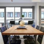 Konferenzraum mit großem Holztisch und hellen Fenstern. Foto: Stephen Dietl