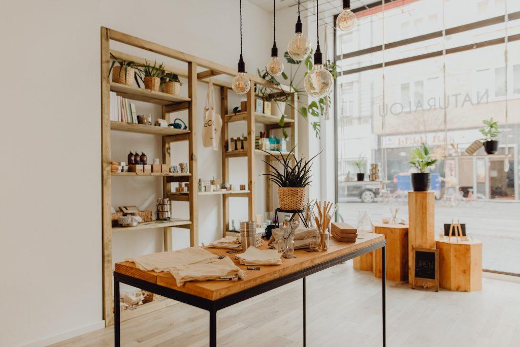 Die Inneneinrichtung des Ladens naturalou. Ein Holzregal, davor ein Tisch, auf dem verschiedene Produkte dekoriert sind. Im Fenster hängen Blumen.