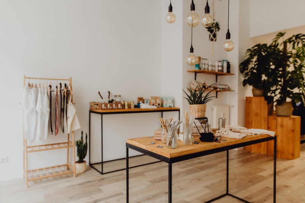 Inneneinrichtung naturalou: Im Vordergrund ein Holztisch mit Produkten, an der Wand steht ein zweiter Tisch sowie eine Kleiderstange, an der einige Kleidungsstücke hängen.