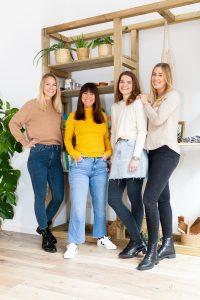 Vier junge Frauen stehen in einem hellen Raum und lachen in die Kamera.