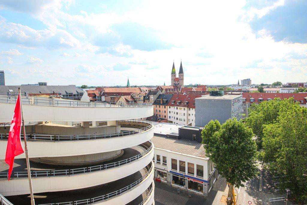 Fotografiert vom Parkhausdeck: Links im Bild die weiß betonierte Parkhausspindel, im Hintergrund die Türme von St. Martini.