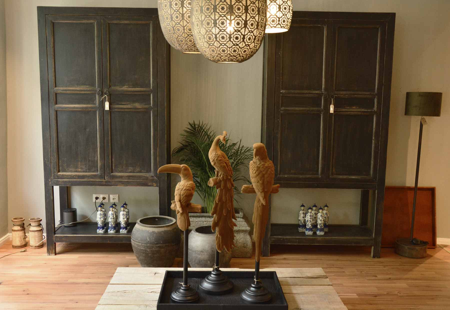 Blick in den Concept-Store mit zwei Vitrinen an der Wand. Im Vordergrund eine Skulptur mit Vögeln.