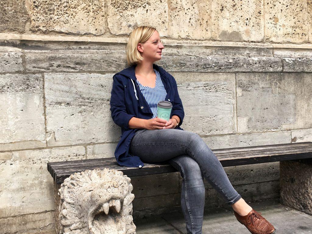 Autorin sitzt auf einer Bank vor dem Dom mit Mehrwegbecher in der Hand.