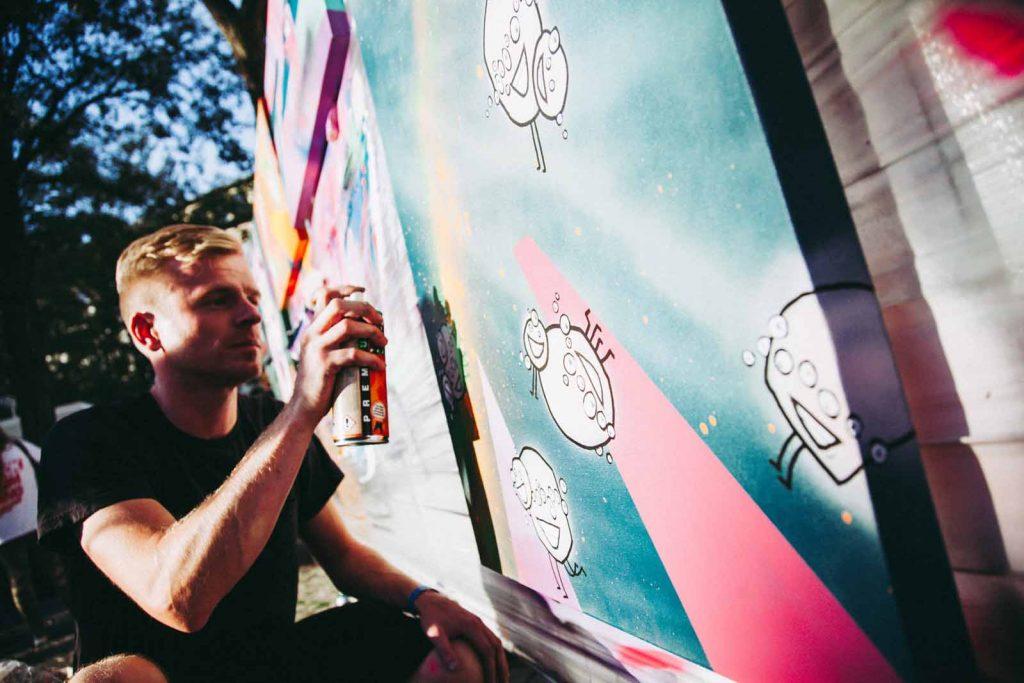 Graffiti-Künstler mit Spraydose vor Bild.