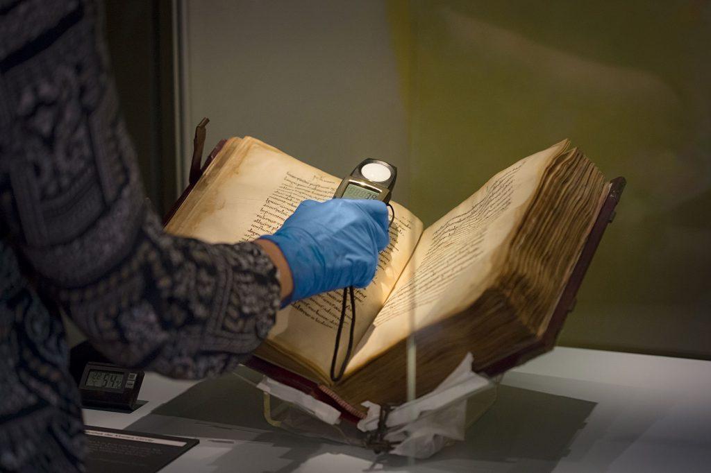 Ein altes Buch liegt aufgeschlagen da. Im Anschnitt ein Arm, in dessen Hand ein Messgerät die Lichtverhältnisse misst.