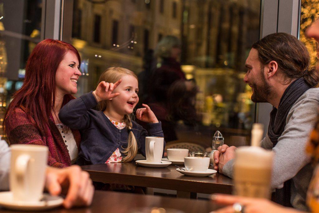 Ein kleines Mädchen sitzt bei der Mutter auf dem Schoss an einem Tisch im Café. Gegenüber sitzt der Vater. Auf dem Tisch stehen Tassen und Becher.