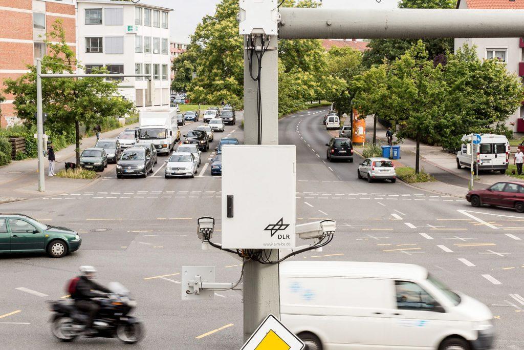 """Straßenkreuzung in Braunschweig, an einer Ampel hängt ein grauer Kasten mit dem Aufdruck """"DLR""""."""