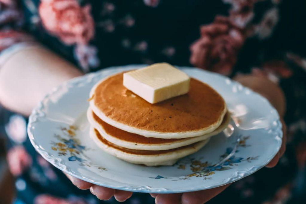 Kleine Pfannkuchen auf einem Porzellanteller.