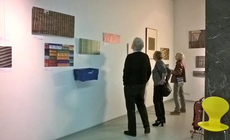 Drei Personen schauen sich Kunstewrke in einem Ausstellungsraum an.