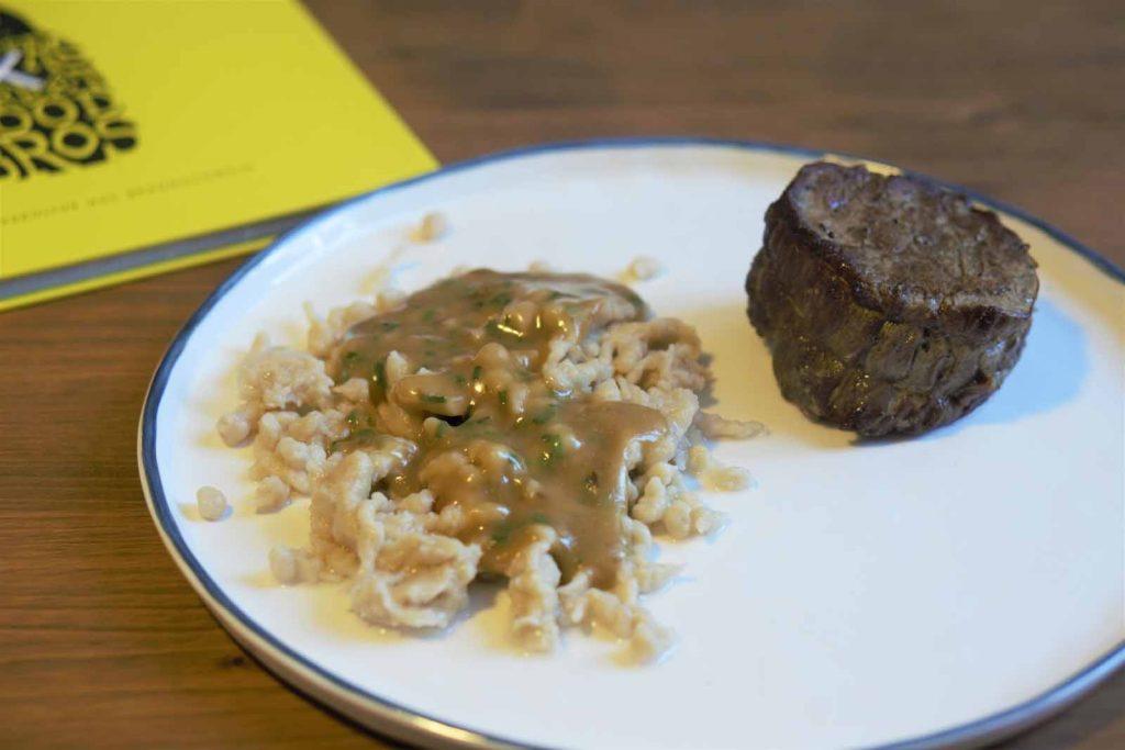 Teller mit Käsespätzle und Rindfleisch.