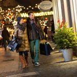 Ein Paar schlendert am Abend durch die Innenstadt. Im Hintergrund leuchten Lichter vom Weihnachtsmarkt.