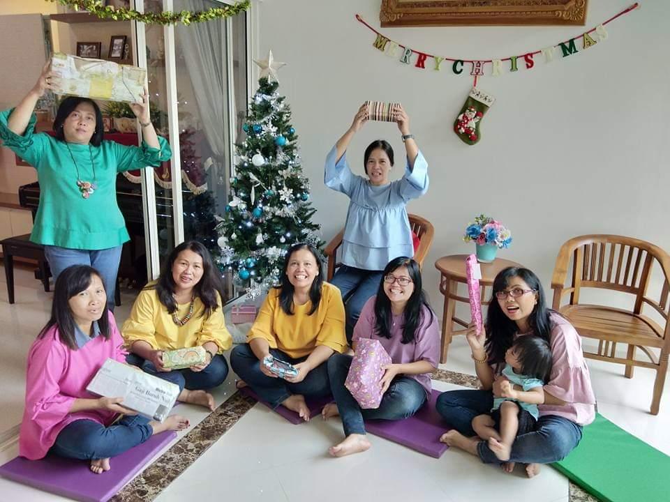 Fünf Frauen in farbenfroher Kleidung sitzen auf dem Fußboden, dahinter stehen zwei Frauen, in der Mitte ein Weihnachtsbaum. Alle Frauen halten Geschenke in der Hand.