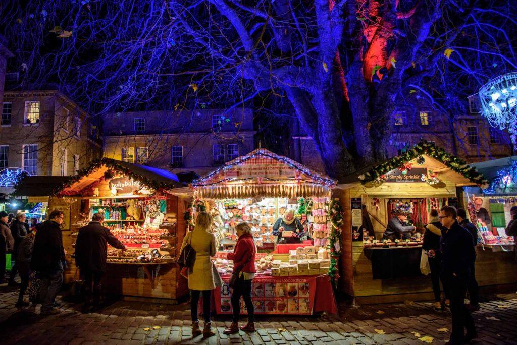 Beleuchtete Weihnachtsmarktstände unter einem großen Baum.