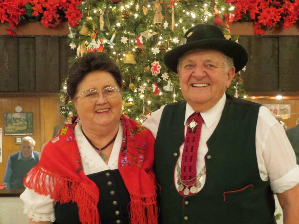 Ein Ehepaar in Tracht vor einem geschmückten Weihnachtsbaum.