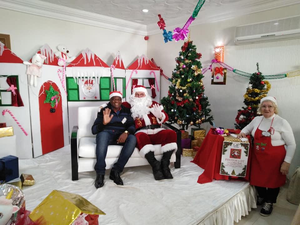 Weihnachtsmann auf einem Sofa, daneben posiert ein Tourist.