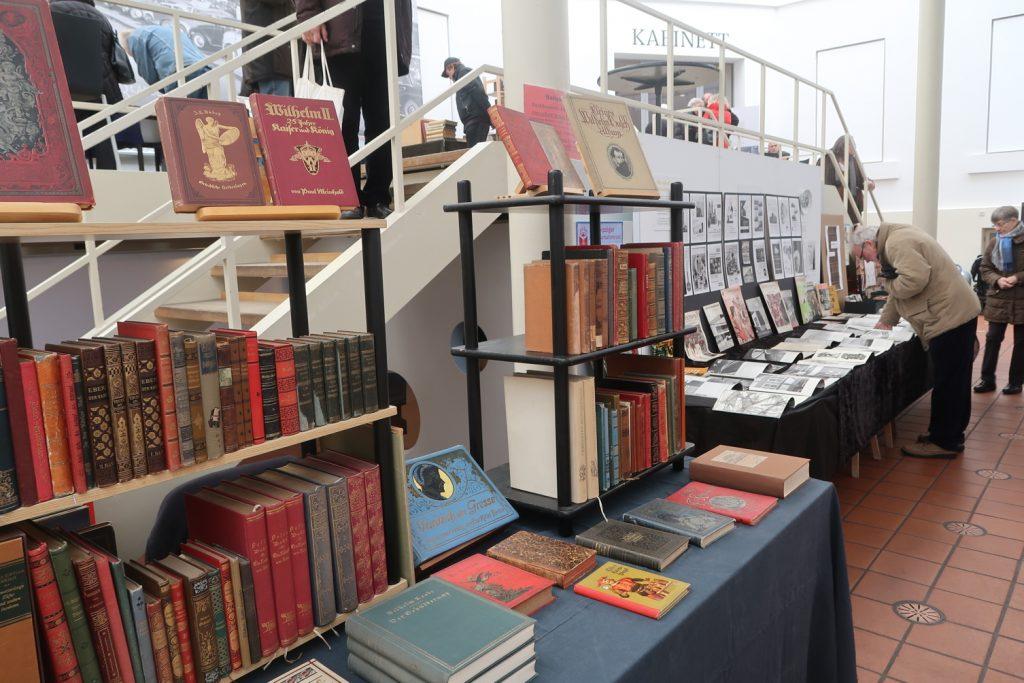 Blick auf Tische mit Büchern. Einige Menschen stöbern an den Tischen in Büchern.
