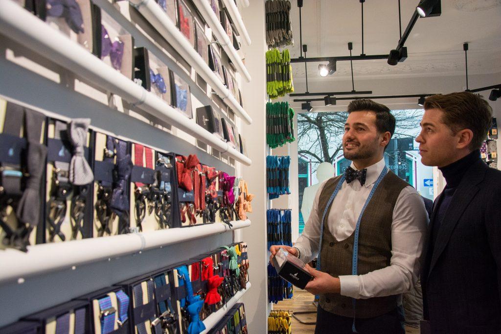 Zwei Männer vor einer Wand bunter Accessoires: Fliegen in verschiedenen Farben, im Hintergrund bunte Socken.