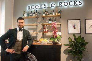 Ein Mann im grünen Anzug, weißem Hemd und Fliege steht an einem schwarzen Tresen. An der Wand im Hintergrund leuchten die Worte Rooks & Rocks.