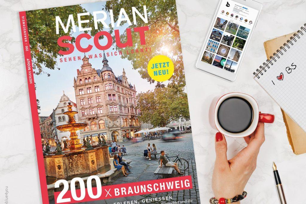 Das Heft MERIAN Scout Braunschweig liegt auf einem Tisch, daneben eine Hand, die einen Kaffee hält, ein Handy und ein Notizblock.