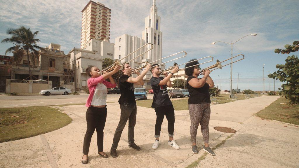 Vier Personen stehen in Havanna auf einem Gehweg und spielen Posaune.