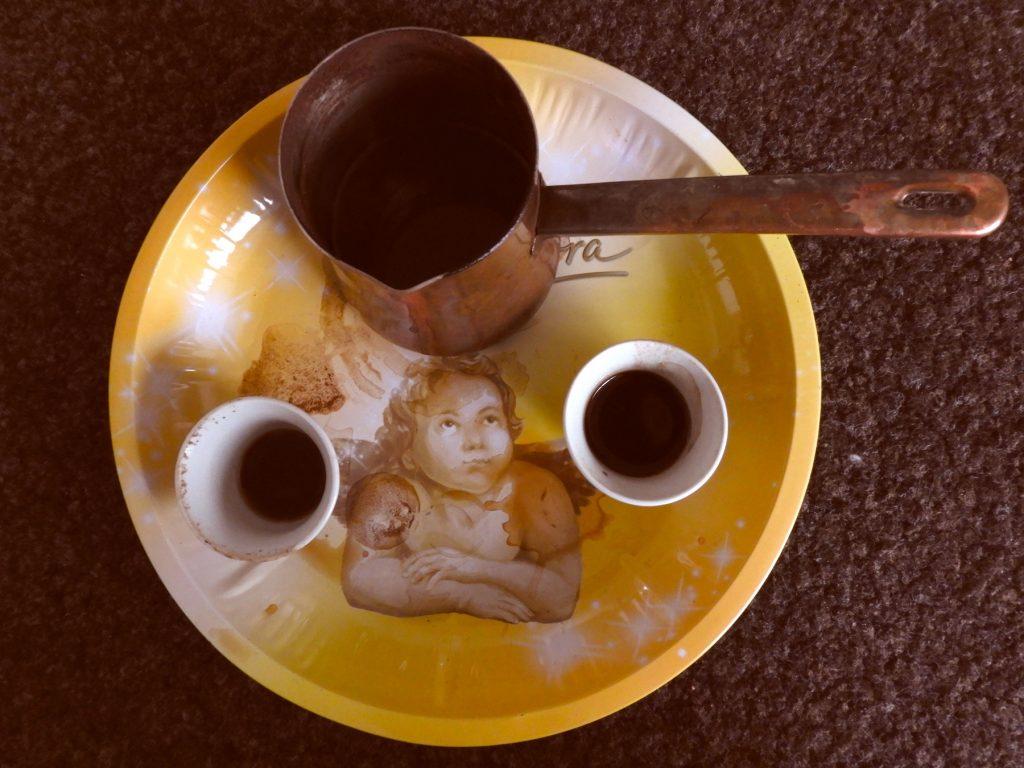 Ein Weihnachtsteller, darauf ein abgenutzter Kaffeetopf aus Kupfer und zwei weiße Mocca-Tassen mit einem Rest Mocca.