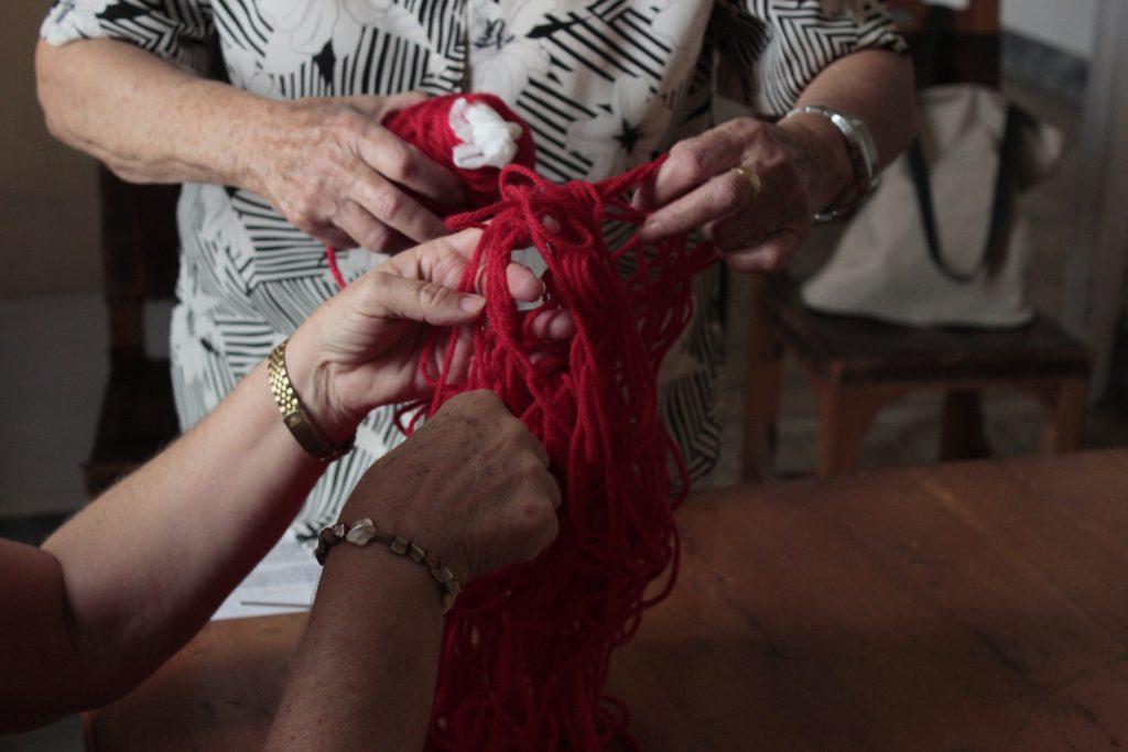 Zwei ältere Damen entwirren ein rotes Wollknäuel.