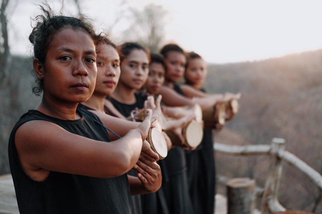 Sechs Frauen, schwarz gekleidet, hintereinanderstehend, schauen in die Kamera. Das Bild wird nach hinten unscharf.