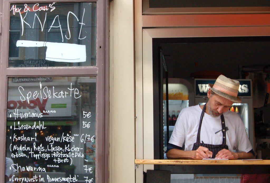 Ein Mann steht hinter einer Fenstertheke, links daneben eine Speisekarte.