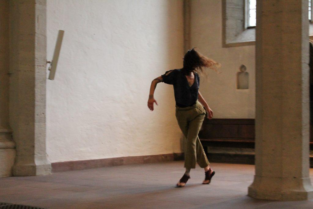 Tänzerin in einem leeren, kargen Raum. Ein Fenster oben rechts verrät, dass es sich um eine Kirche handelt.