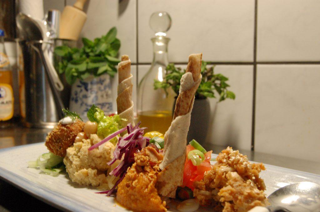 Ein Teller mit Hummus und arabischem Fladenbrot.