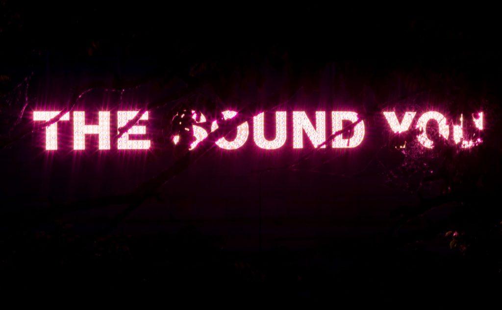 Das Bild ist fast schwarz, nur die Wörter The Sound You leuchten pink.