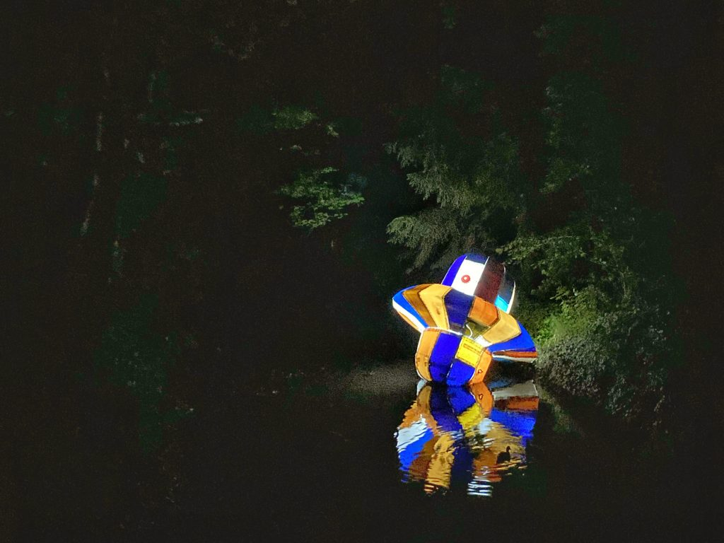 Ein bunter, beleuchteter, überdimensionaler Kreisel liegt auf der Wasseroberfläche des Fluss Oker. Die Umgebung ist nachtschwarz.