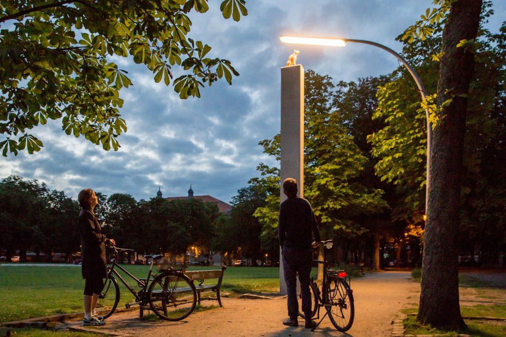 Zwei Fahrradfahrer stehen vor einer Skulptur: Auf einem Sockel sitzt eine Katze, die von einer Straßenlaterne angestrahlt wird.