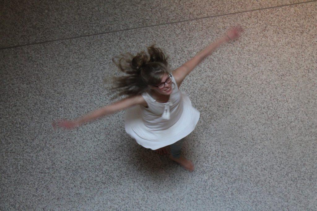 Frau im weißen Kleid dreht eine Pirouette.