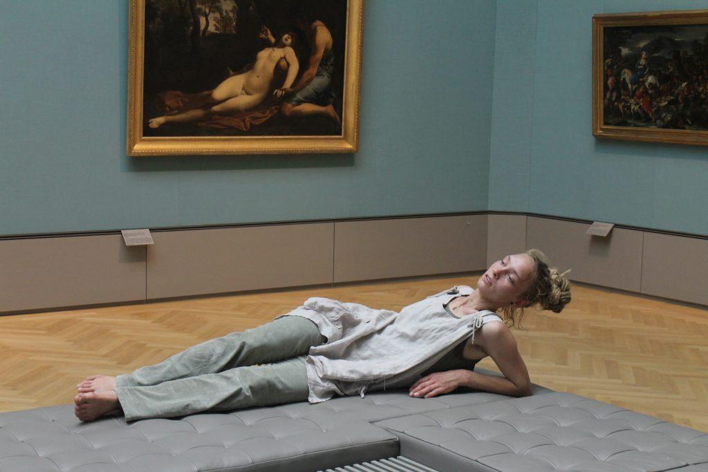 Frau liegt auf einer gepolsterten Sitzbank. Im Hintergrund ein Gemälde. Die Frau auf dem Gemälde und die Frau auf der Sitzbank nehmen die gleiche Position ein.