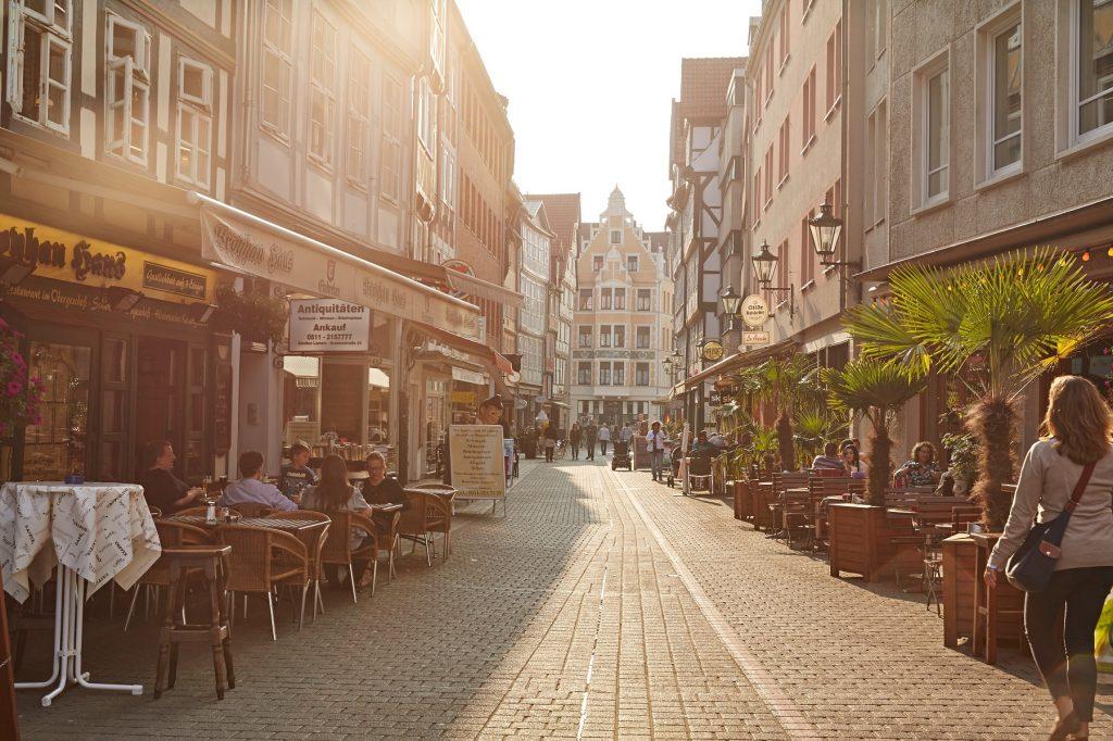 Straßenzug mit Cafés an beiden Seiten.