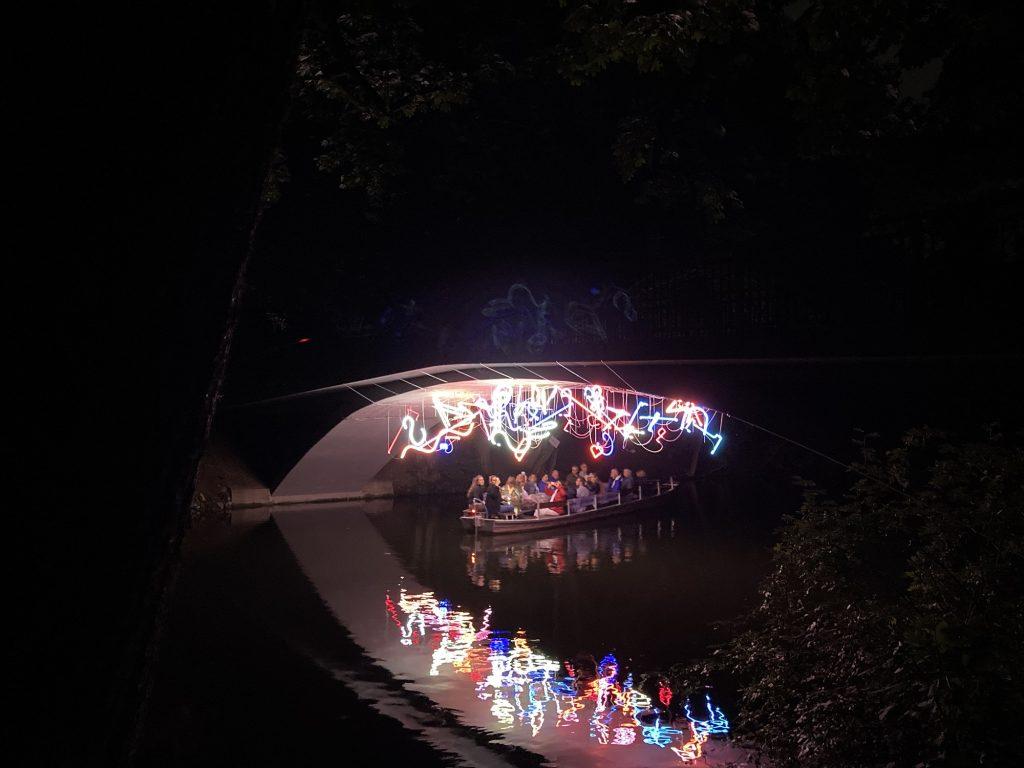Bunte Lichter unter einer Brücke. Darunter ein Kahn mit Menschen.