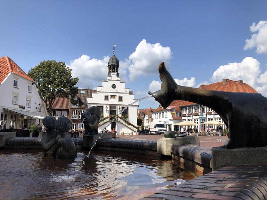 Im Vordergrund ein Brunnen, dahinter das weiße Historische Rathaus mit dem Glockenturm von Lingen.