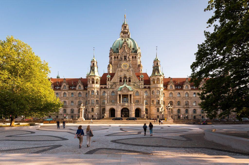 Hannover Rathaus im Goldenen Licht. An den Seiten jeweils ein Baum.